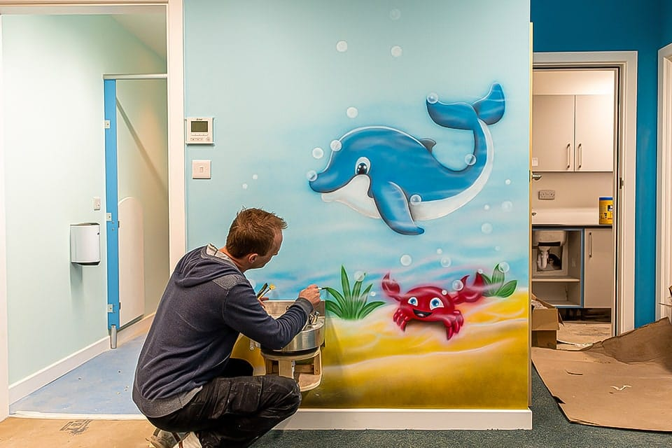 mural artist painting dolphin mural FB