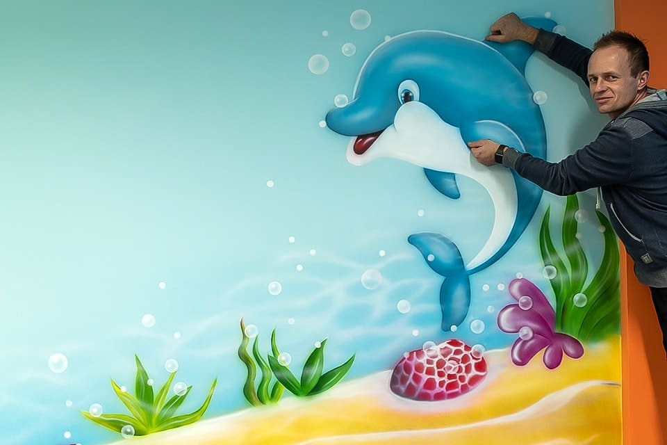 mural artist with dolphin mural FB